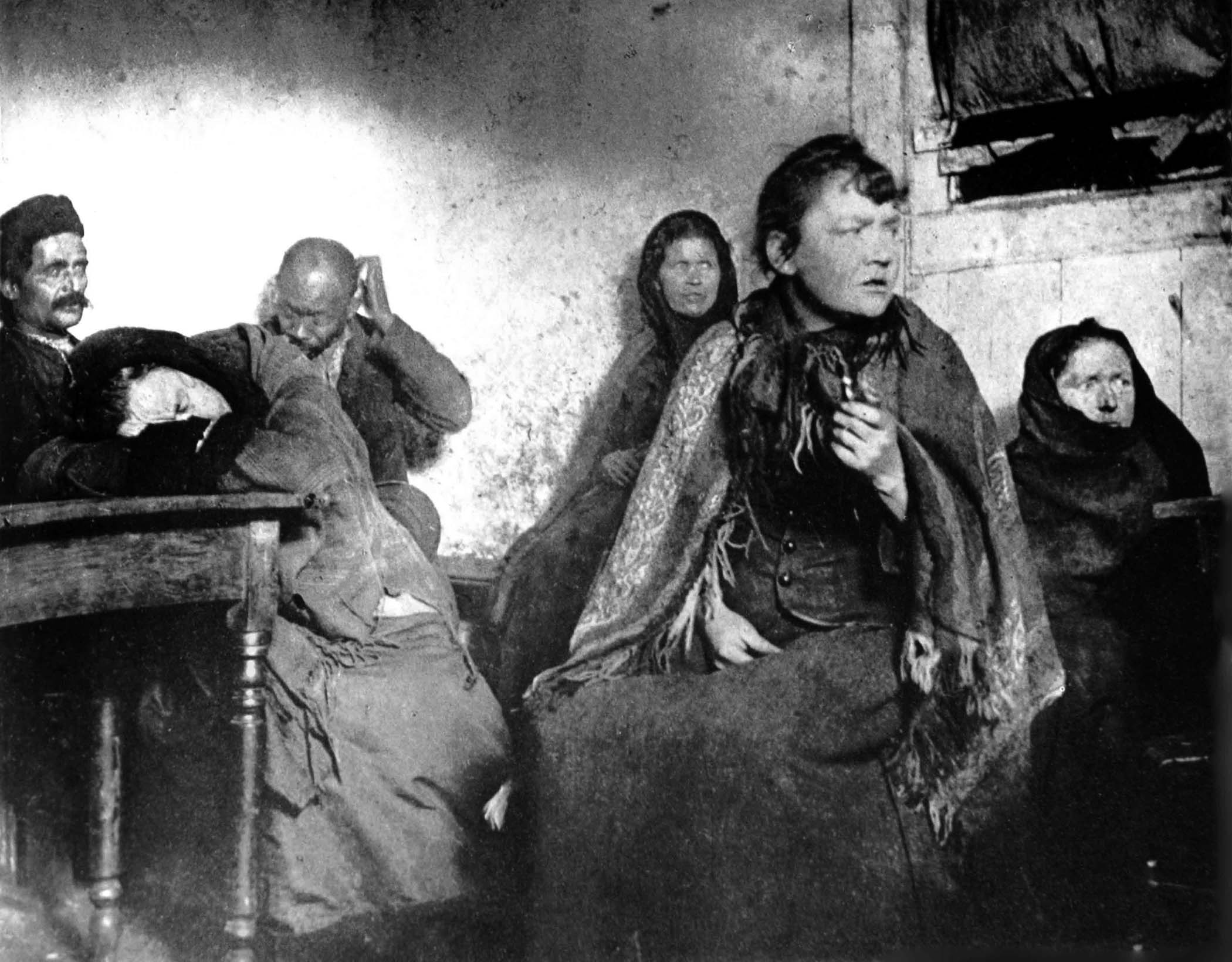 Hell on earth. Homeless women sit all night in unheated basement dives. Photo made possible by Jacob Riis' introduction of flash photography in the United States journalism.