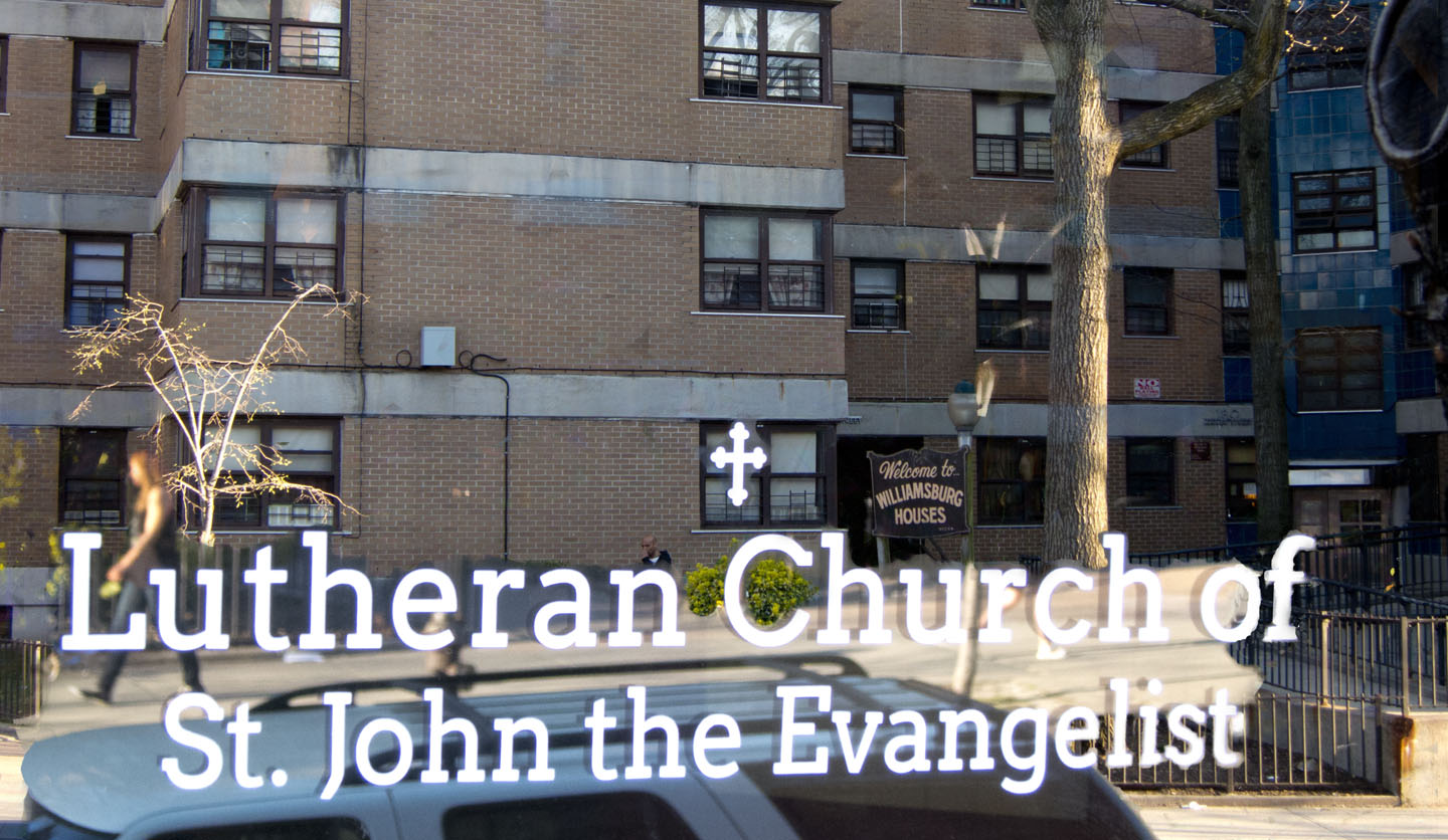 Looking at Williamsburg Houses in reflection of church door. Photo illustration by Tony Carnes/A Journey through NYC religions