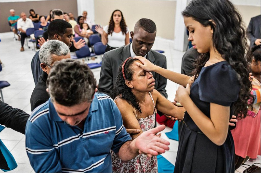 Alani Santos blessing attendees of a Monday-night miracles and healing service as they pray. Photo: Sebastian Liste/Noor Images, for The New York Times