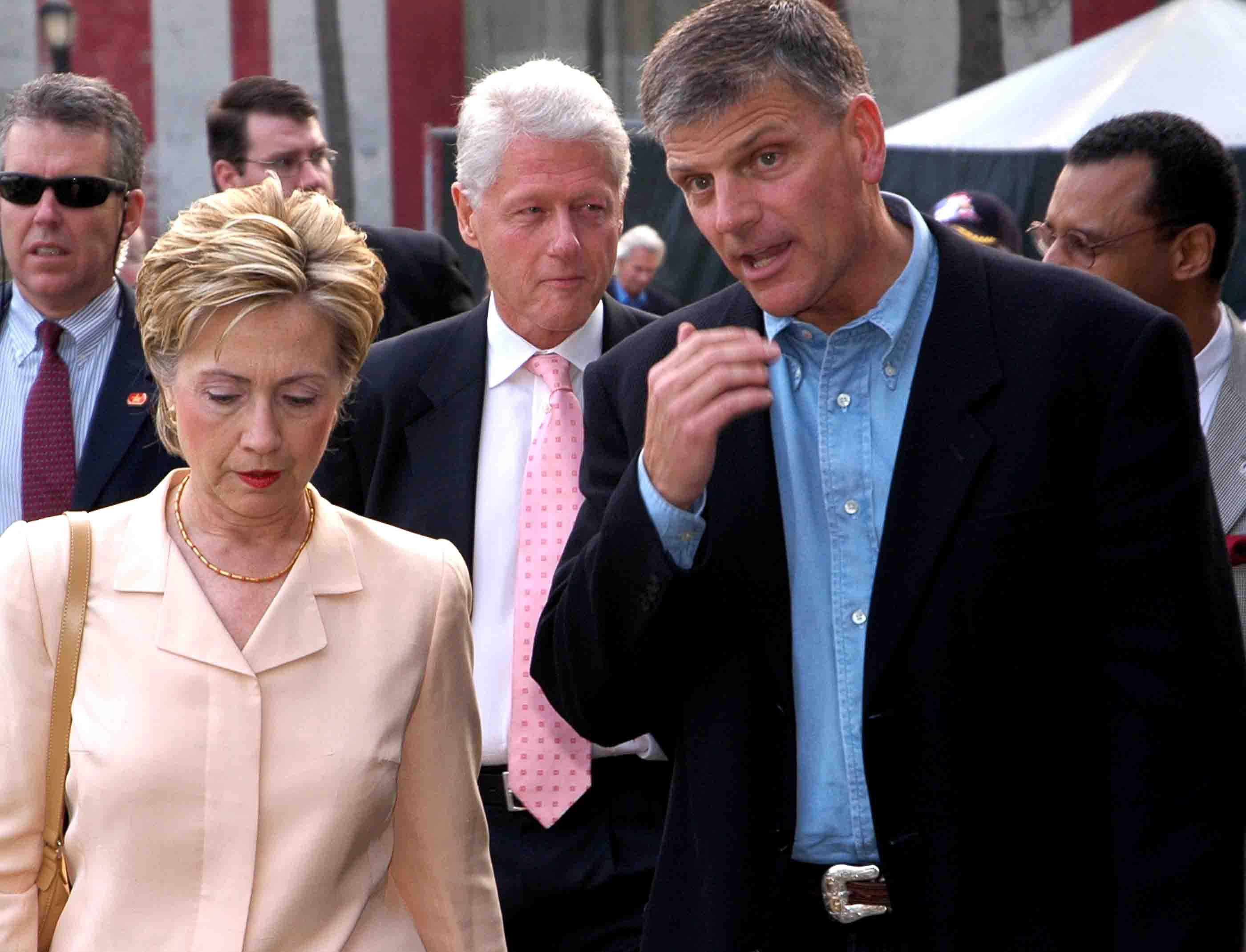 Hilary Clinton says that she has long admired evangelist Billy Graham, but voters are uncertain about her faith. Here she walks with Franklin Graham, with her husband and Rev. A.R. Bernard of the Christian Cultural Center in the background. At Billy Graham Crusade, New York City, 2006. Photo: Tony Carnes/A Journey through NYC religions