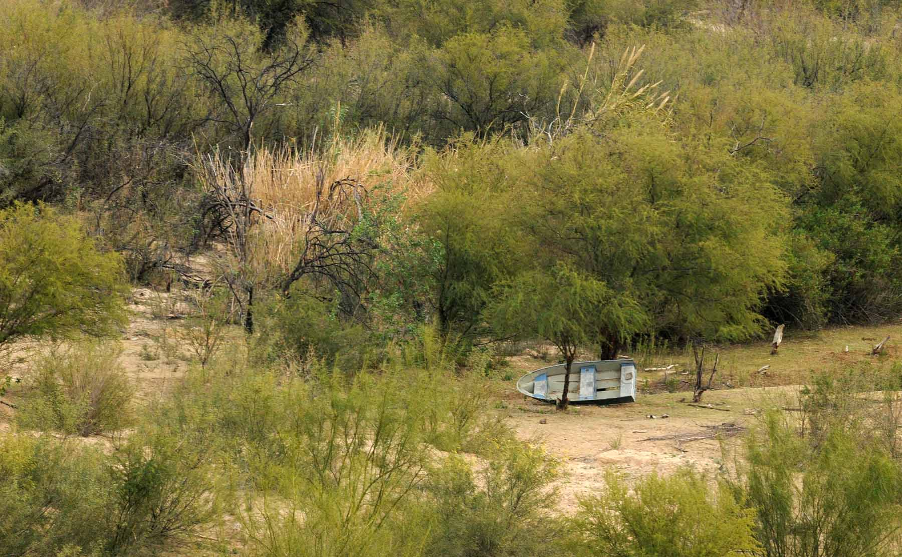 Smuggler boat laying in wait under trees in Mexico near Rio Grande River. Javi used an used tire raft to come across. Photo: Tony Carnes/A Journey through NYC religions